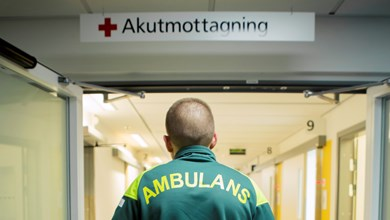 Person med tröja där det står ambulans, står under akutmottagning-skylt